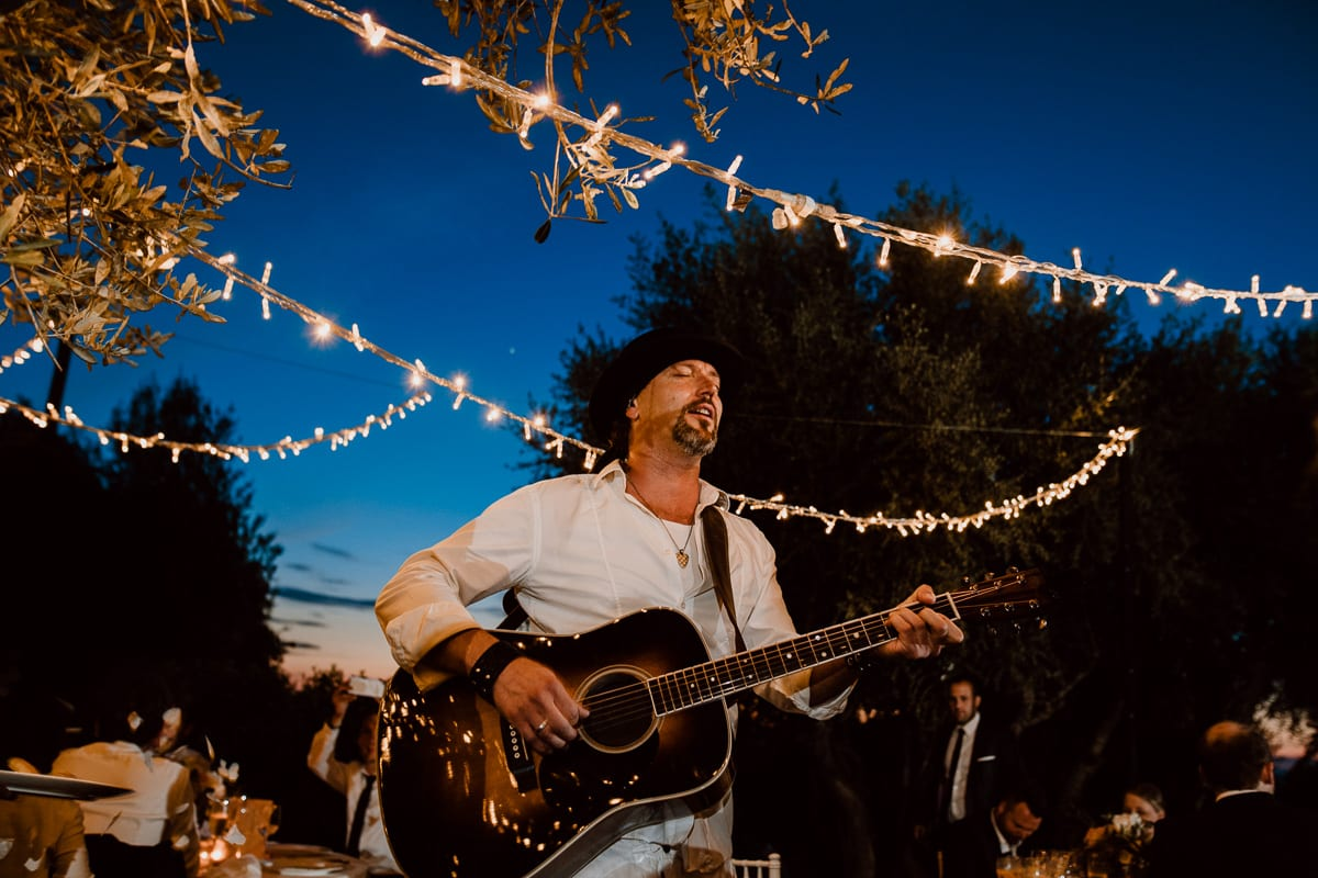 A singer with a guitar accompanies the guests during the wedding dinner.