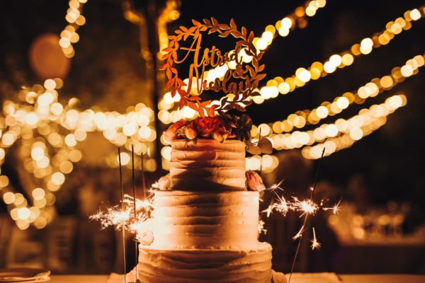 The wedding cake in front of fairy lights with burning sparklers.