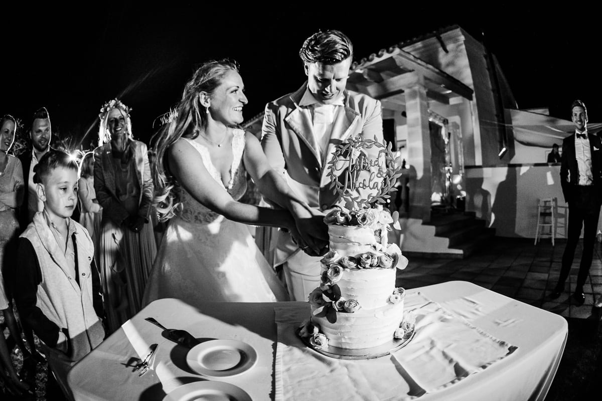 The laughing bride and groom cutting the wedding cake.