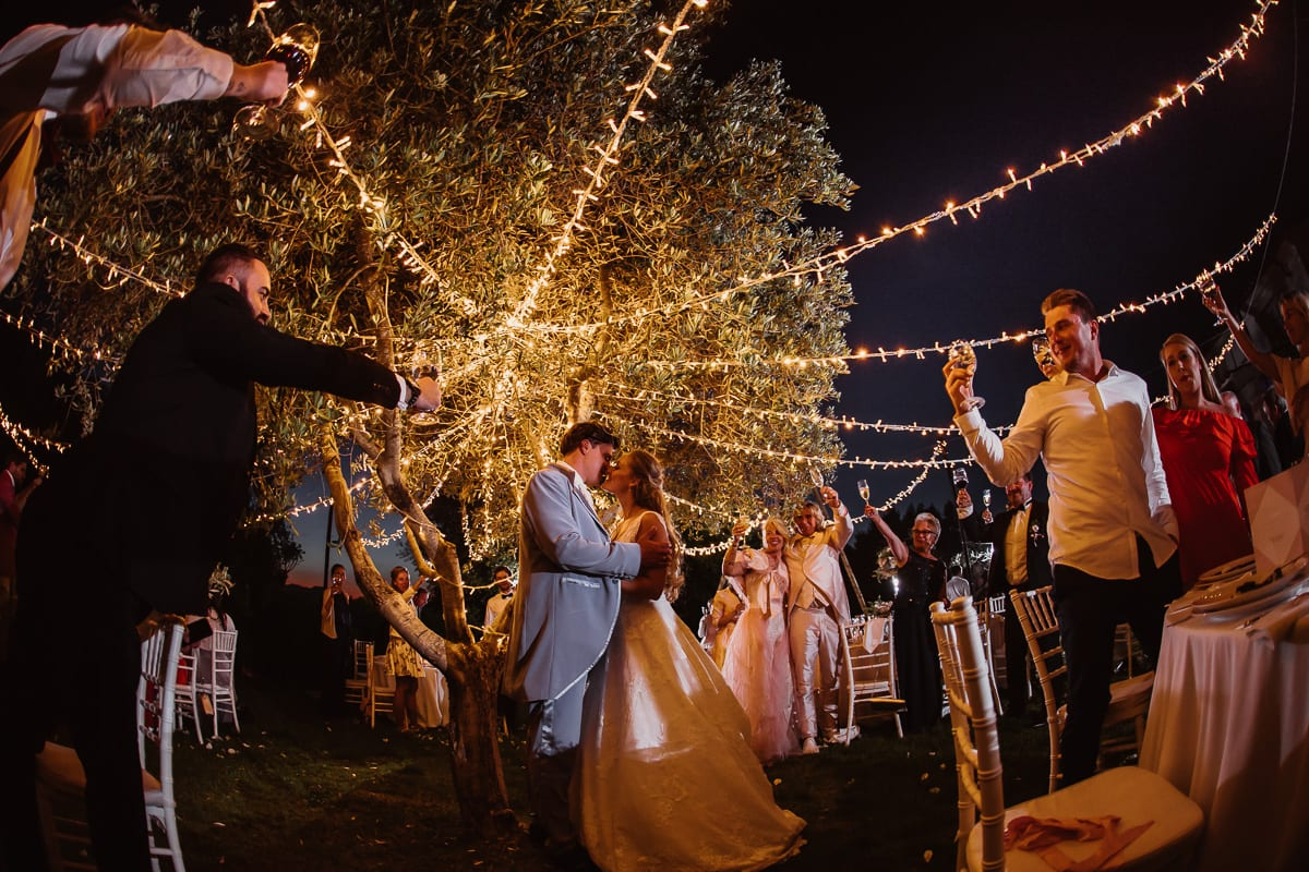 The bride and groom kissing under the romantic fairy lights surrounded by all wedding guests which are raising the glasses.