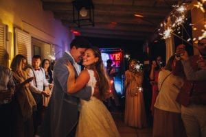 The newlywed wedding couple is dancing surrounded by their guests and sparklers.