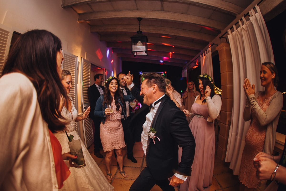 The father of the bride dancing surrounded by young female guests.
