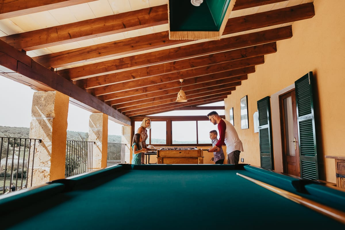 A family of the guests playing with their two children on the finca at table football.