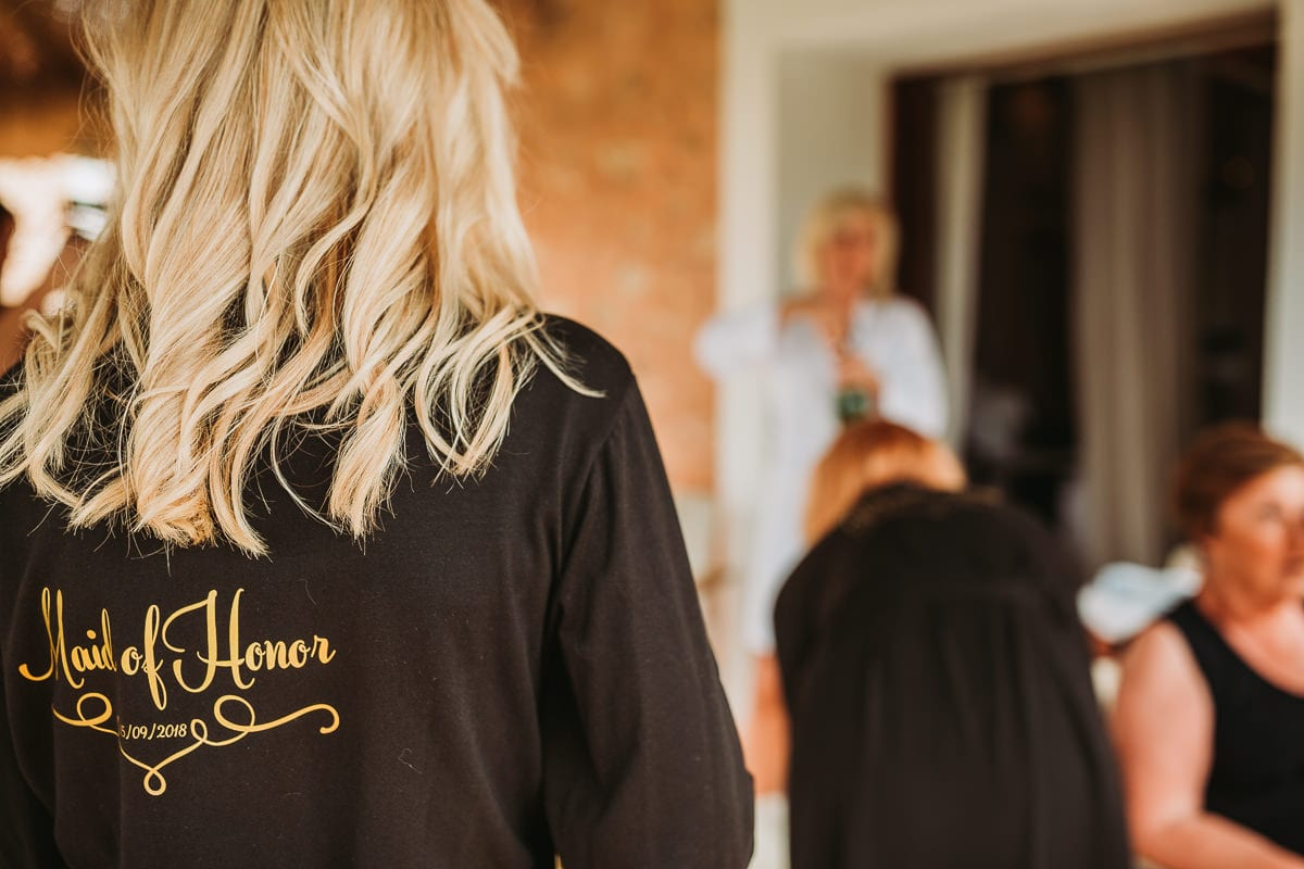 Close up from behind of the bridesmaids morning coat with golden letters maid of honor.