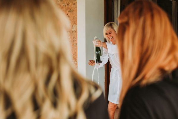 The bride is laughing about the overflowing champagne bottle.