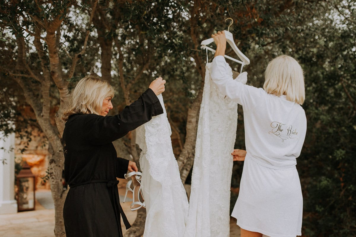The bride and her mom hang the wedding dress outside to give it a fresh breeze.
