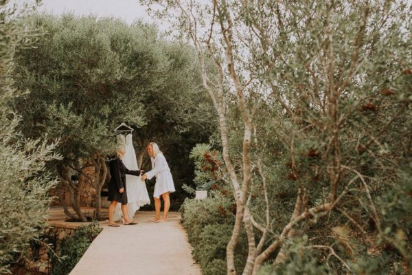 The bdrial dress is hanging on a olive tree. The bride and her mother are laughing.