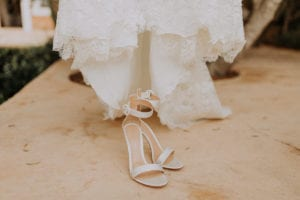 Close up of the bridal shoes in front of the wedding dress.