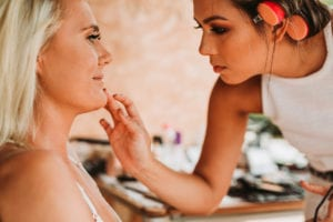 Portrait during the make up of the bride and her make up artist.