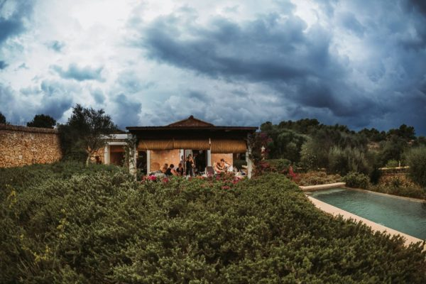 Wide angle view through the green plants to the house where the bride is made up. We see a dramatic cloudy sky.