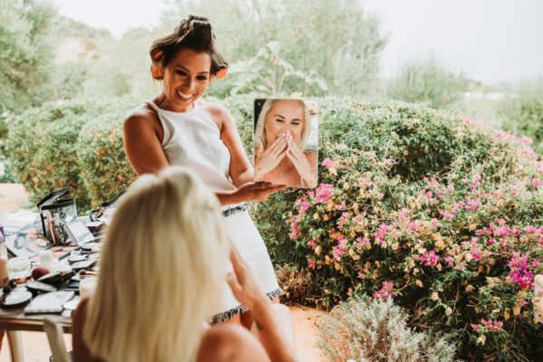 The make up artist lift up a mirror that the bride can see the result. She is smiling very happy.