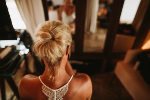 Bride from behind after the first step of the hair styling.