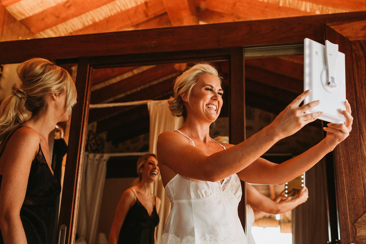 The very happy bride is looking with a mirror at her hairstyle.