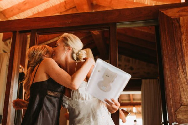The bride is hugging and kissing her hair stylist.