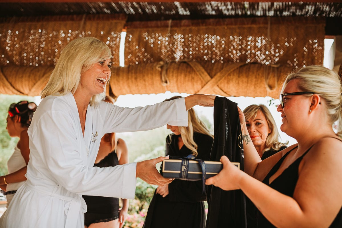 The bride is giving a gift to her bridesmaids.