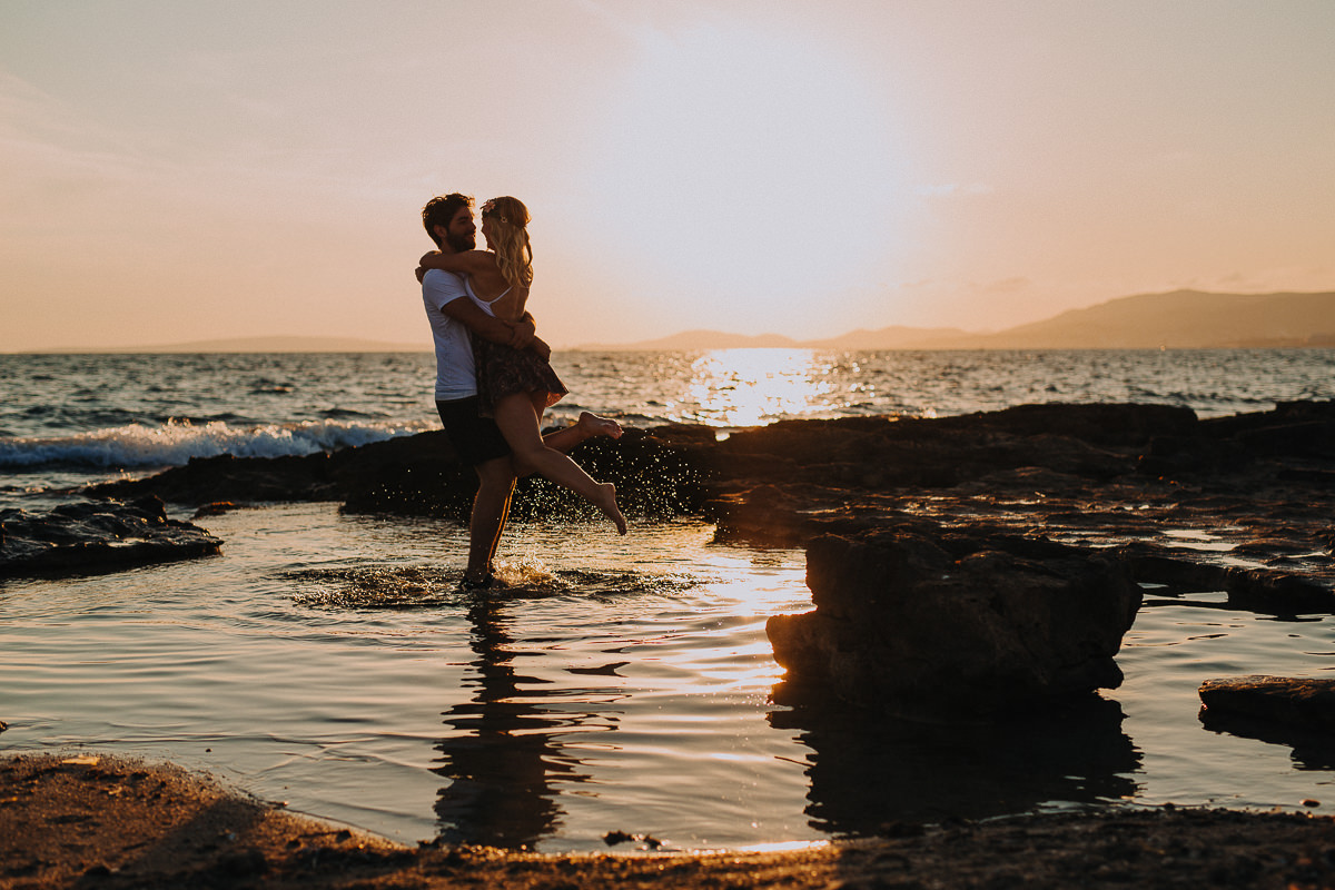 Beautiful young couple in love having fun on the beach standing in the water during the orange sunset.