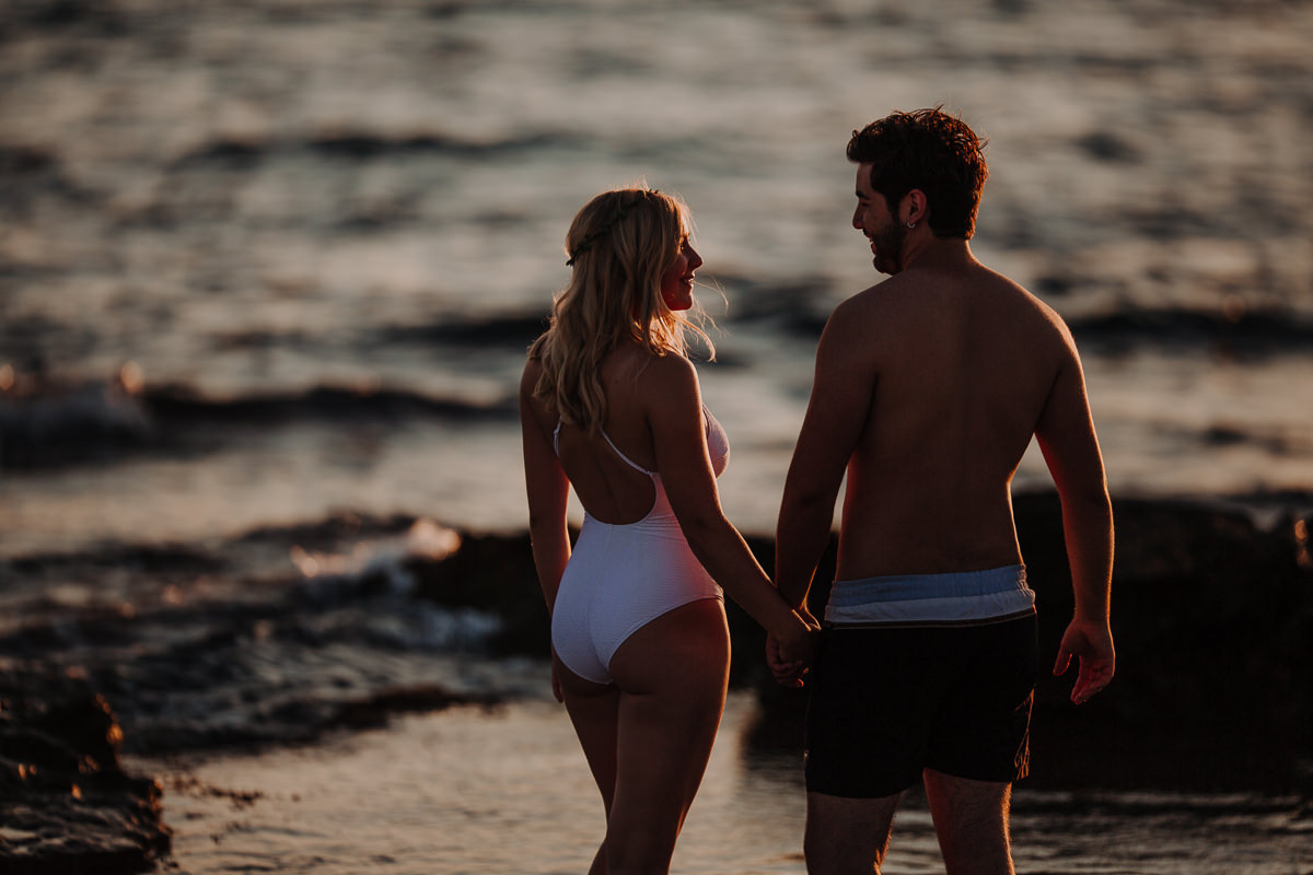 Young couple from behind standing in the water.