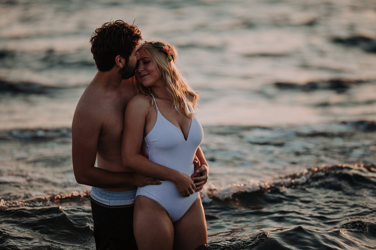 Intimate scene of the couple standing in the water on the beach.