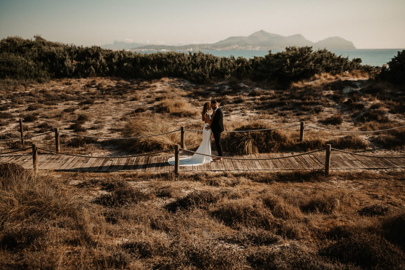 Bridal couple in the middle of the dunes closed to the beach in Alcudia