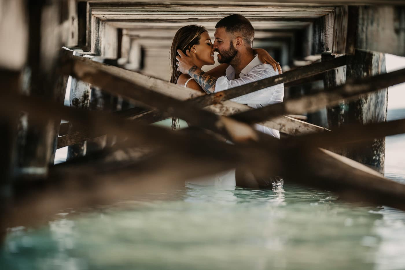 Kissing bridal couple in te water on the beach