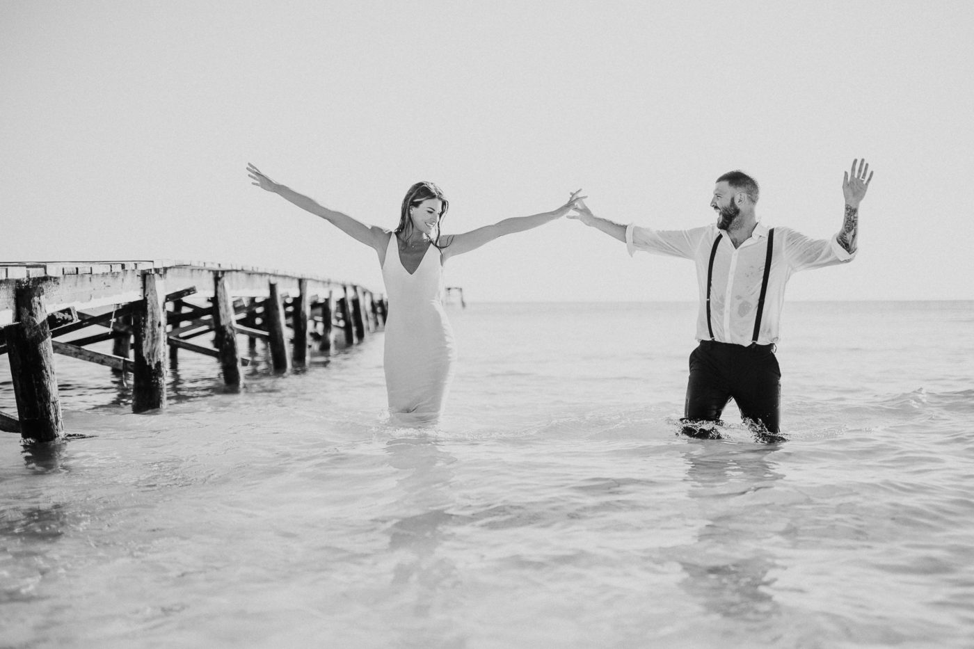 Happy bridal couple in the water rising up the arms